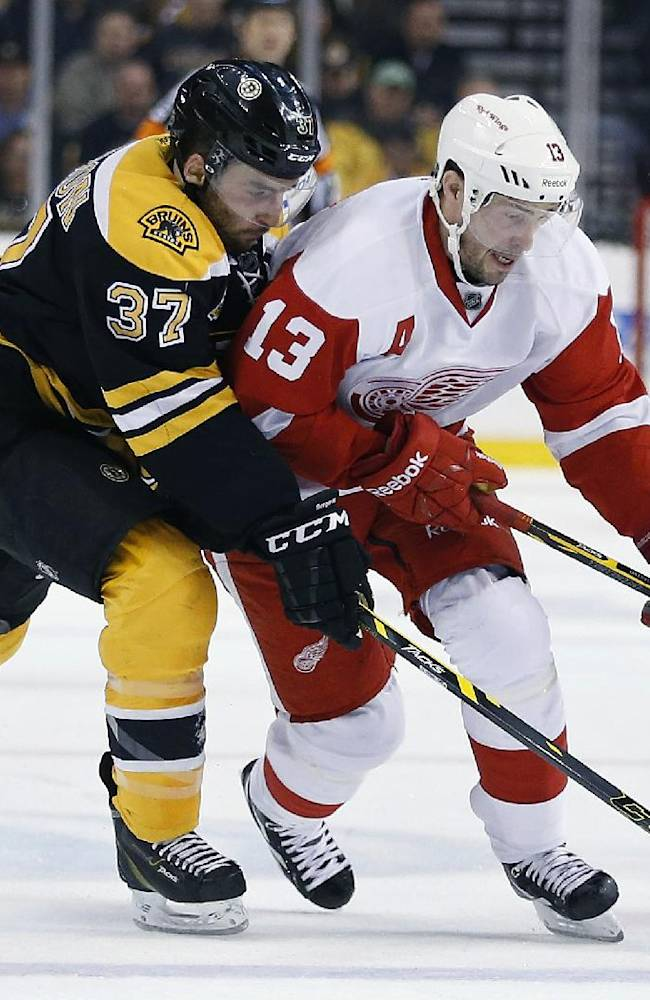 Boston Bruins' Patrice Bergeron (37) and Detroit Red Wings' Pavel Datsyuk (13) battle for the puck during the first period in Game 5 in the first round of the NHL hockey Stanley Cup playoffs  in Boston, Saturday, April 26, 2014