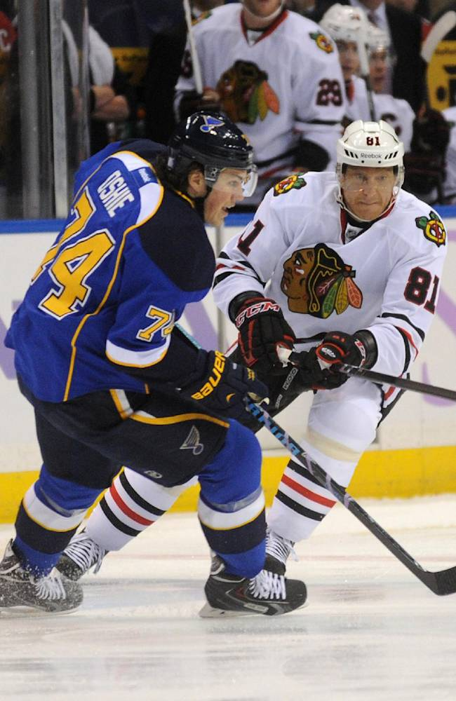 Chicago Blackhawks' Marian Hossa (81), of Slovakia, passes around St. Louis Blues' T.J. Oshie during the first period of an NHL hockey game Wednesday, Oct. 9, 2013, in St. Louis