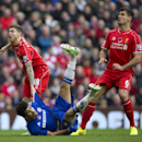 Chelsea's Diego Costa, bottom, is held by Liverpool's Alberto Moreno, left, as Dejan Lovren looks on during the English Premier League soccer match between Liverpool and Chelsea at Anfield Stadium, Liverpool, England, Saturday Nov. 8, 2014