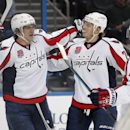 Washington Capitals left wing Alex Ovechkin (8), of Russia, celebrates his goal against the Tampa Bay Lightning with teammates defenseman John Carlson (74) and defenseman Brooks Orpik (44) during the first period of an NHL hockey game Tuesday, Dec. 9, 201