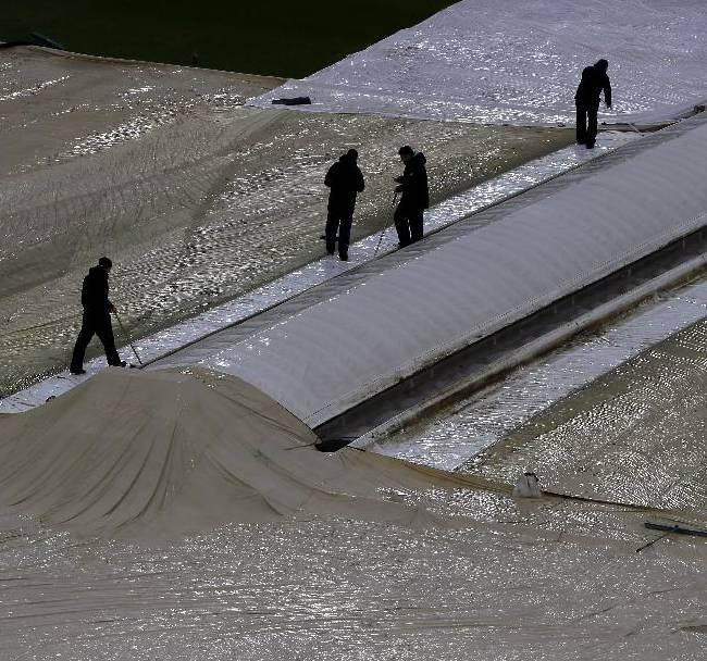 Ground staff are silhouetted as they work to keep water off the plastic covers over the wicket after rain stopped play during the third one day international cricket match between England and Australia, at Edgbaston cricket ground in Birmingham, England, Wednesday, Sept. 11, 2013