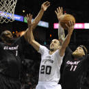 San Antonio Spurs guard Manu Ginobili, center, of Argentina, shoots against Miami Heat forwards Chris Bosh, left, and Chris Andersen, during the first half of an NBA basketball game on Thursday, March 6, 2014, in San Antonio. (AP Photo/Darren Abate)