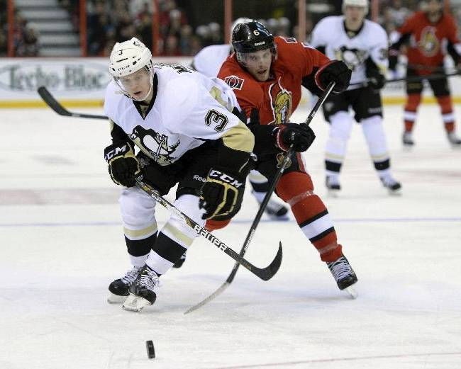 Pittsburgh Penguins' Olli Maatta, left, holds Ottawa Senators' Bobby Ryan off the puck during the second period of an NHL hockey game in Ottawa, Ontario on Monday, Dec. 23, 2013