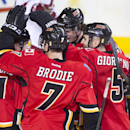 Calgary Flames' Mark Giordano, right, celebrates his goal against the Phoenix Coyotes with Mikael Backlund, left, from Sweden, TJ Brodie, second from left, and Joe Colborne during second period NHL action Wednesday, Dec. 4, 2013 in Calgary, Alberta The As
