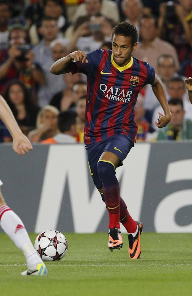 Barcelona's Neymar, center, tries to pass Ajax's Christian Poulsen, left, and Ajax's Ricardo Van Rhijn, right, during the Champions League group H soccer match between Ajax Amsterdam and F.C. Barcelona on Wednesday, Sept. 18, 2013, at Camp Nou stadium in Barcelona, Spain