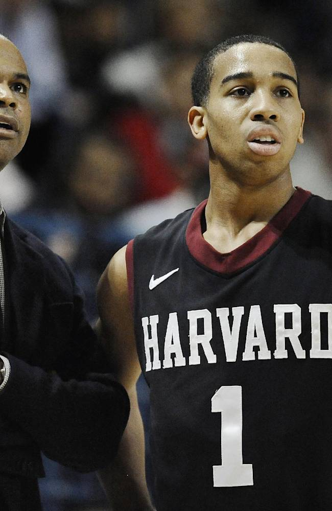 Harvard head coach Tommy Amaker, left, talks with player Siyani Chambers during the first half of an NCAA college basketball game, Friday, March 7, 2014, in New Haven, Conn