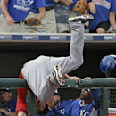 Los Angeles Angels third baseman David Freese dives over a dugout railing as he tries to catch a foul ball by Kansas City Royals' Eric Hosmer during the sixth inning of a spring exhibition baseball game Thursday, March 20, 2014, in Surprise, Ariz The Asso
