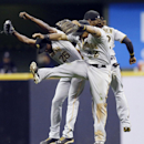 Pittsburgh Pirates' Felix Pie (26), Marlon Byrd (2) and Andrew McCutchen celebrate their 4-3 win over the Milwaukee Brewers in a baseball game Tuesday, Sept. 3, 2013, in Milwaukee. (AP Photo/Morry Gash)