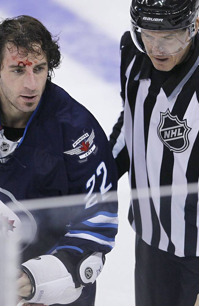 Winnipeg Jets' Chris Thorburn (22) is lead to the penalty box after a fight with Detroit Red Wings' Jordin Tootoo (22) during first period NHL action in Winnipeg on Monday, Nov. 4, 2013