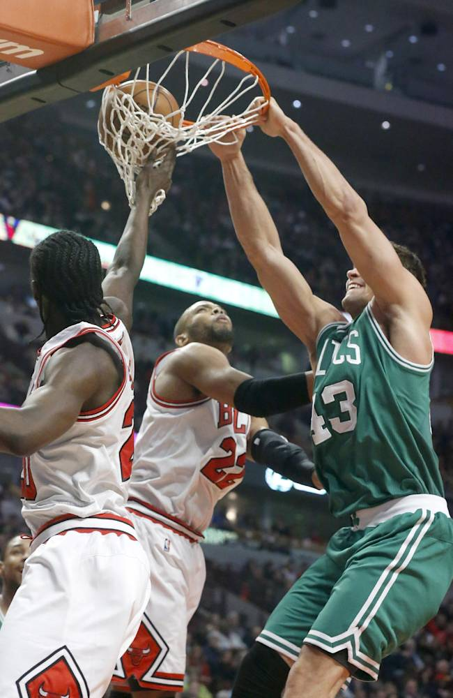 Boston Celtics power forward Kris Humphries, right, dunks the ball over Chicago Bulls shooting guard Taj Gibson (22) and Tony Snell during the first half of an NBA basketball game on Thursday, Jan. 2, 2014, in Chicago