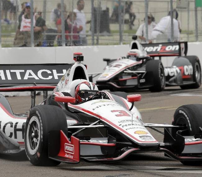 Helio Castroneves (3), of Brazil leads Will Power (12), of Australia, into turn 10 during practice for the IndyCar Firestone Grand Prix of St. Petersburg auto race Friday, March 28, 2014, in St. Petersburg, Fla
