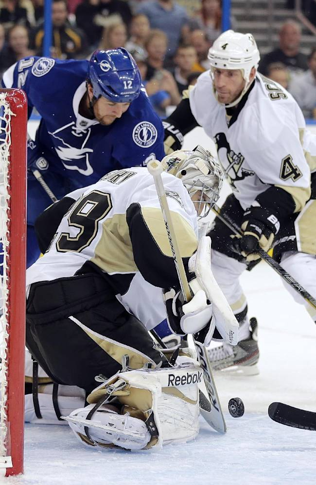 Pittsburgh Penguins goalie Marc-Andre Fleury (29) makes a save on a shot by Tampa Bay Lightning left wing Ryan Malone (12) during the second period of an NHL hockey game on Saturday, Oct. 12, 2013, in Tampa, Fla. Penguins defenseman Rob Scuderi (4) moves in