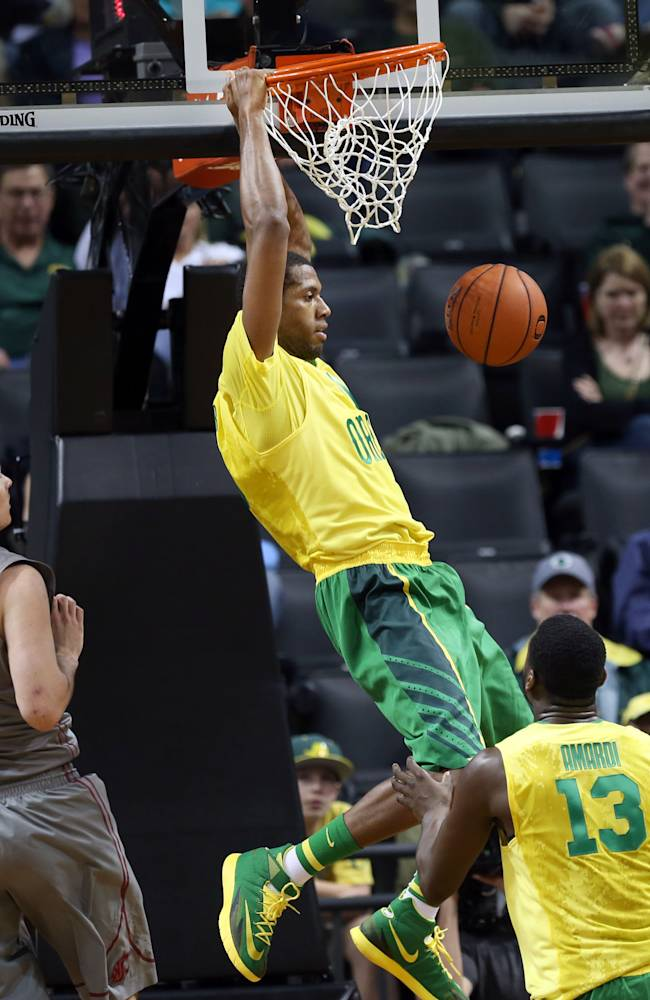 Oregon's Mike Moser, center, dunks the ball past Washington State's Brett Boese, left, and Richard Amardi, right, during the second half of an NCAA college basketball game in Eugene, Ore., Sunday, Feb. 23, 2014