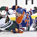 Minnesota Wild's Mikael Granlund (64) is hit by Edmonton Oilers' Andrew Ference (21) during third period NHL hockey action in Edmonton, Alberta, on Thursday Feb. 27, 2014 The Associated Press