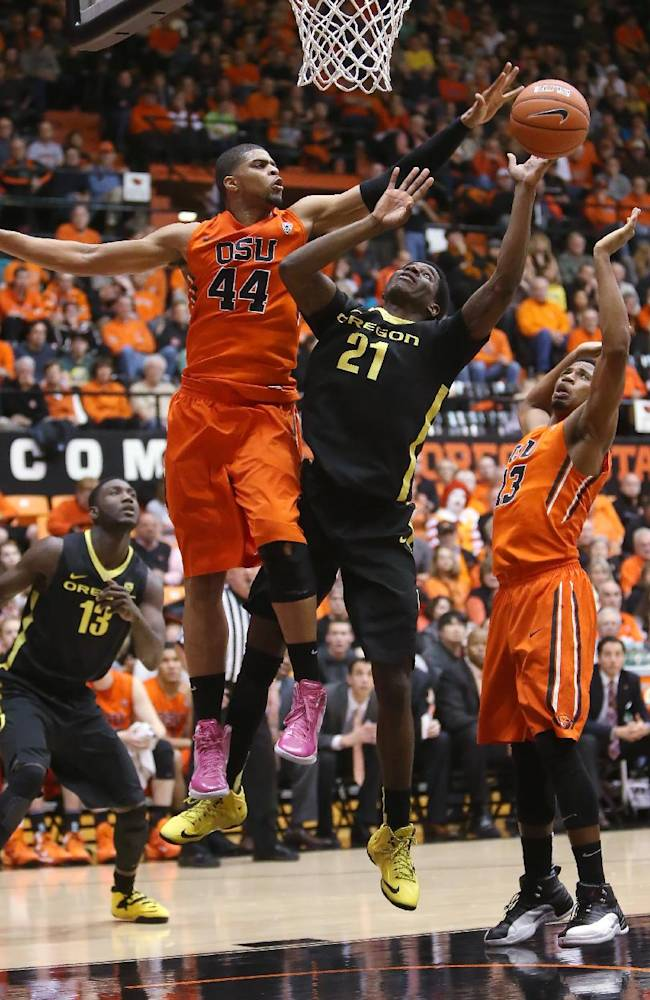 Oregon State's Devon Collier (44) blocks a shot by Oregon's Damyean Dotson (21) during an NCAA men's basketball game at Gill Coliseum in Corvallis, Ore. on Sunday, Jan. 19, 2014. Oregon lost 80-72 to Oregon State