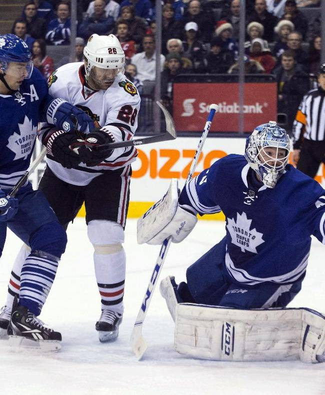 Toronto Maple Leafs goaltender Jonathan Bernier, right, stretches to make a save as Chicago Blackhawks' Michal Handzus, center, and Leafs' Joffrey Lupul skate near during the first period of an NHL hockey game in Toronto on Saturday, Dec. 14, 2013