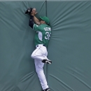 Boston Red Sox center fielder Grady Sizemore (38) catches a fly ball while hitting the center field wall off the bat of St. Louis Cardinals Daniel Descalso in the first inning of an exhibition baseball game in Fort Myers, Fla., Monday, March 17, 2014. The