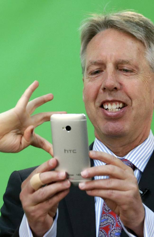 Seattle Storm head coach Brian Agler smiles as he is shown how to take a selfie at the team's annual media day Wednesday, May 7, 2014, in Seattle. The team opens against the Los Angeles Sparks on May 16 in Seattle