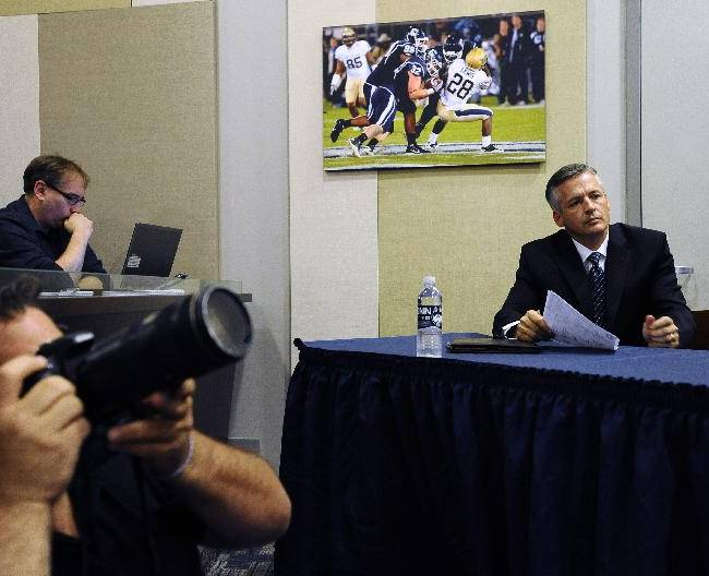 Connecticut interim head coach and former offensive coordinator T.J. Weist, right, sits at an NCAA college football news conference, Monday, Sept. 30, 2013, in  Storrs, Conn. Weist is taking over for fired coach Paul Pasqualoni