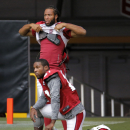 Arizona Cardinals wide receiver Larry Fitzgerald, standing, and cornerback Patrick Peterson watch their teammates during NFL football training camp, Monday, Aug. 11, 2014, in Glendale, Ariz The Associated Press