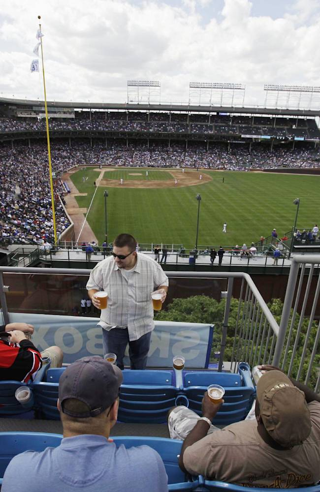 In this Sept. 3, 2010, file photo, spectators enjoy the view from one of the many rooftop bleachers along Sheffield Avenue outside Wrigley Field during a Chicago Cubs baseball game in Chicago. The Cubs have asked the city's permission to put a 650-square-foot sign at Wrigley Field that may partially block views of the field from the surrounding rooftop businesses.  The club filed a permit application after talks with the rooftop owners fell apart last week.  The rooftop owners have said they will file a lawsuit if the team puts up anything that cuts into their views
