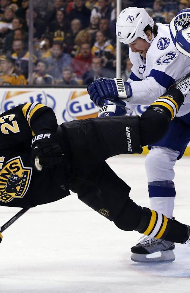 Tampa Bay Lightning left wing Ryan Malone (12) dumps Boston Bruins center Chris Kelly (23) to the ice in front of goalie Anders Lindback during the second period of an NHL hockey game in Boston Monday, Nov. 11, 2013. The Bruins won 3-0