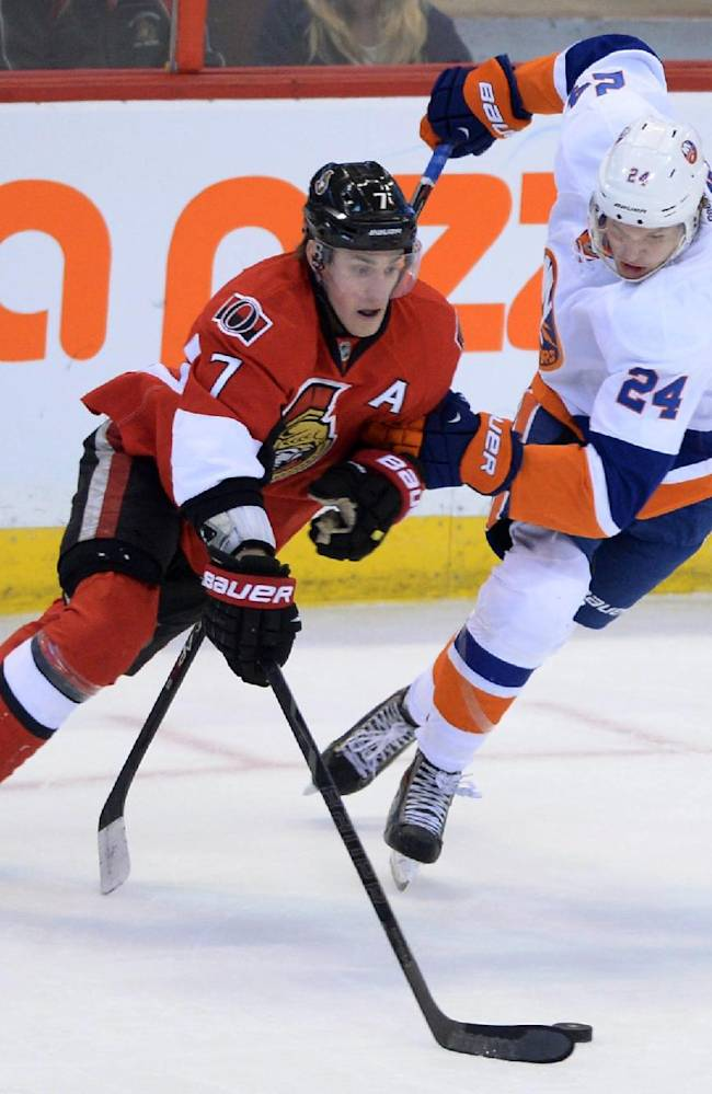 Ottawa Senators' Kyle Turris, left, fights to keep the puck away from New York Islanders' Kevin Czuczman during the second period of an NHL hockey game in Ottawa, Ontario, on Wednesday, April 2, 2014