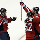 Washington Capitals' Troy Brouwer, right, celebrates teammates Mike Green (52) and Jason Chimera after scoring the winning goal against the Boston Bruins in overtime during a preseason hockey game, Friday, Sept. 26, 2014, in Washington.The Capitals won 5-