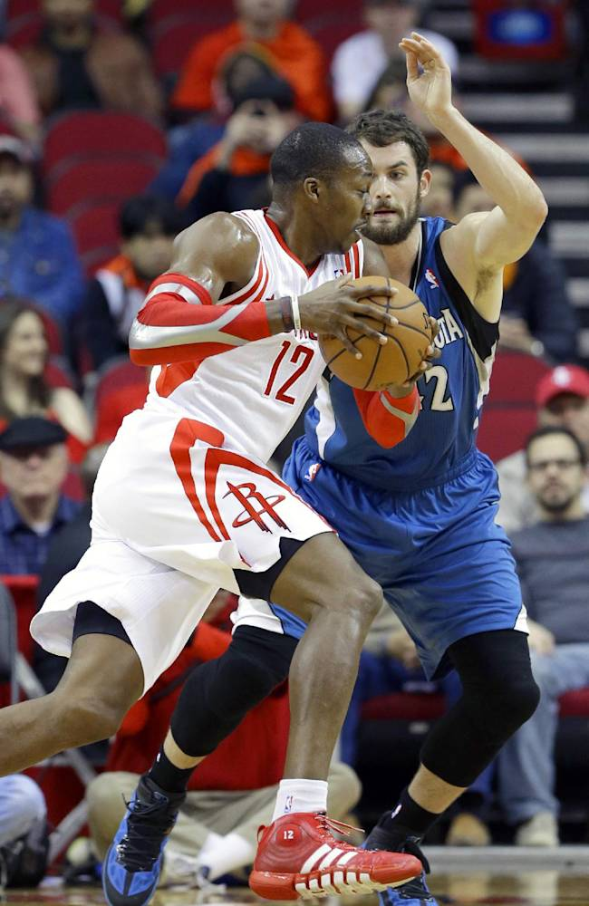 Houston Rockets' Dwight Howard (12) drives the ball past Minnesota Timberwolves' Kevin Love (42) in the first half of an NBA basketball game Saturday, Nov. 23, 2013, in Houston