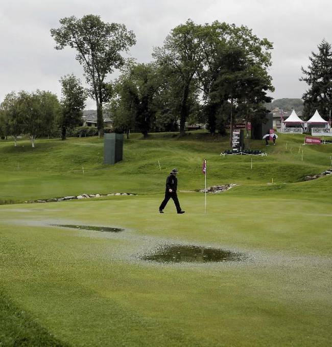 A staff member checks the green during a rain delay in the first round of the Evian Championship women's golf tournament in Evian, eastern France, Thursday, Sept. 12, 2013