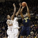 Michigan guard Trey Burke, right, shoots over Purdue defenders Rapheal Davis, center, and Terone Johnson during the second half of an NCAA college basketball game on Wednesday, March 6, 2013, in West Lafayette, Ind. Michigan won 80-75. (AP Photo/AJ Mast)