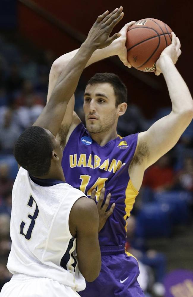 Albany forward Sam Rowley (14) is pressured by Mount St. Mary's guard Sam Prescott (3) in the first half of a first-round game of the NCAA college basketball tournament, Tuesday, March 18, 2014, in Dayton, Ohio