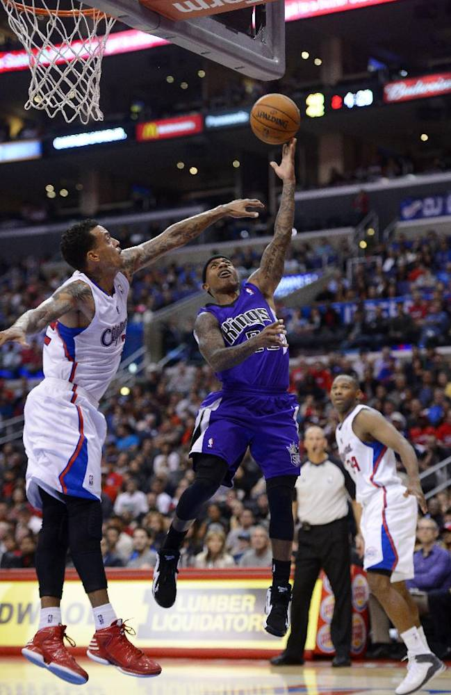 Sacramento Kings point guard Isaiah Thomas, center, puts up a shot as Los Angeles Clippers small forward Matt Barnes, left, defends and shooting guard Willie Green looks on during the first half of their NBA basketball game, Friday, Oct. 25, 2013, in Los Angeles