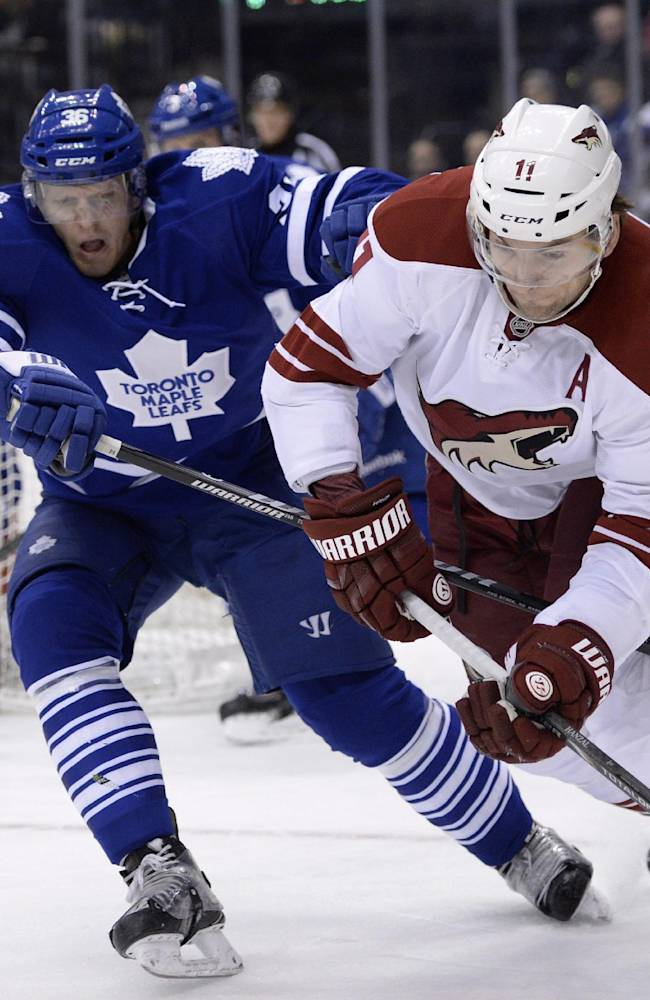 Toronto Maple Leafs' Carl Gunnarsson defends as Phoenix Coyotes' Martin Hanzal (11) controls the puck during the first period of an NHL hockey game action in Toronto on Thursday, Dec. 19, 2013
