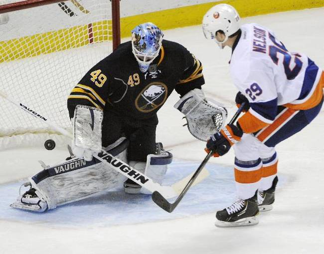 Buffalo Sabres goaltender Connor Knapp (49) gets beat as New York Islanders  center Brock Nelson (29) scores the game winning goal during the team shootout of an NHL hockey game in Buffalo, N.Y., Sunday April 13, 2014. New York won 4-3
