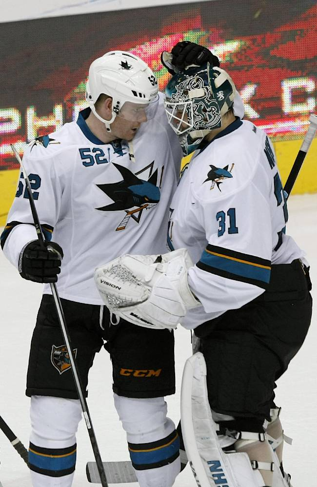 San Jose Sharks goalie Antti Niemi (31) celebrates with Matt Irwin (52) after defeating the Phoenix Coyotes in an overtime shoot-out 4-3, during an NHL hockey game on Friday, Dec. 27, 2013, in Glendale, Ariz