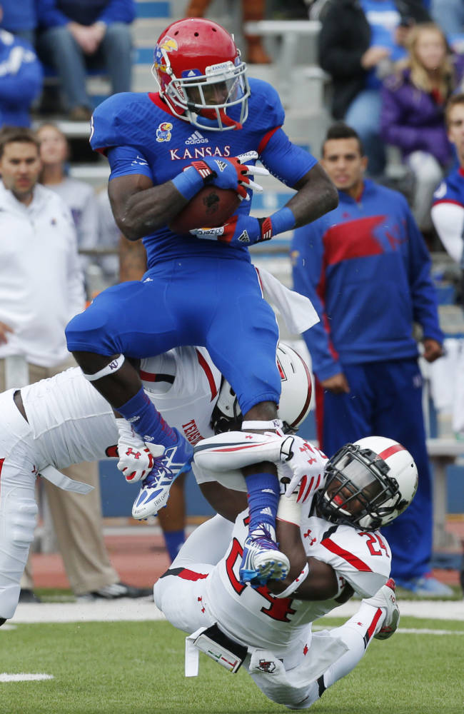 Kansas running back Tony Pierson catches a pass while covered by Texas Tech defensive backs Tre' Porter (5) and Bruce Jones (24) during the first half of an NCAA college football game in Lawrence, Kan., Saturday, Oct. 5, 2013
