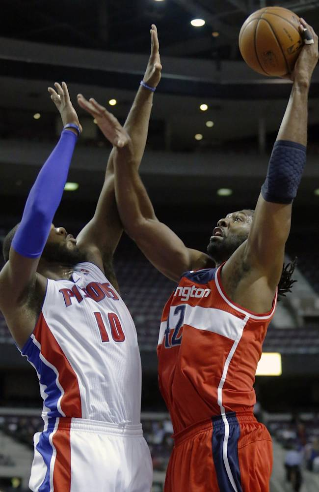 Washington Wizards forward Nene goes to the basket against Detroit Pistons center Greg Monroe (10) during the first half of a preseason NBA basketball game Tuesday, Oct. 22, 2013, in Auburn Hills, Mich