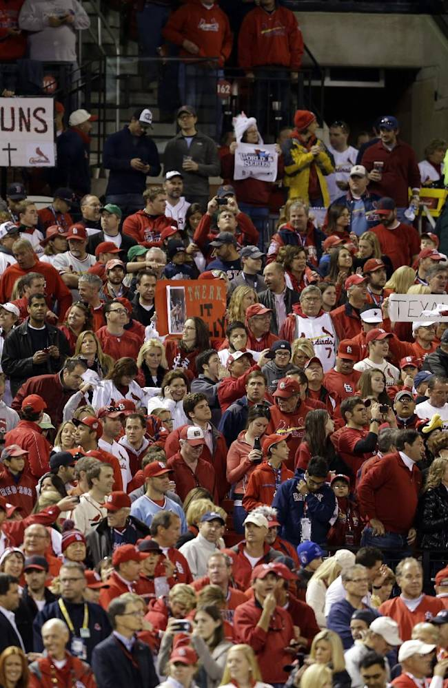 In this Oct. 26, 2013 photo, baseball fans hold up signs as they watch festivities prior to the start of Game 3 of the World Series between the St. Louis Cardinals and the Boston Red Sox in St. Louis