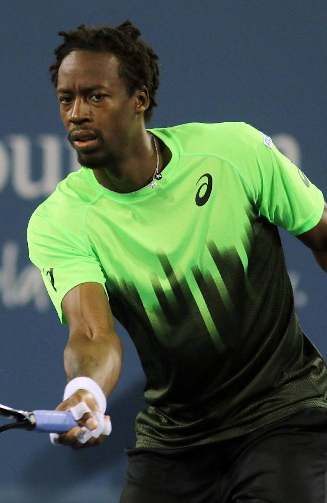 Gael Monfils, of France, returns a volley to Roberto Bautista Agut, of Spain, at the Western & Southern Open tennis tournament, Wednesday Aug. 13, 2014, in Mason, Ohio