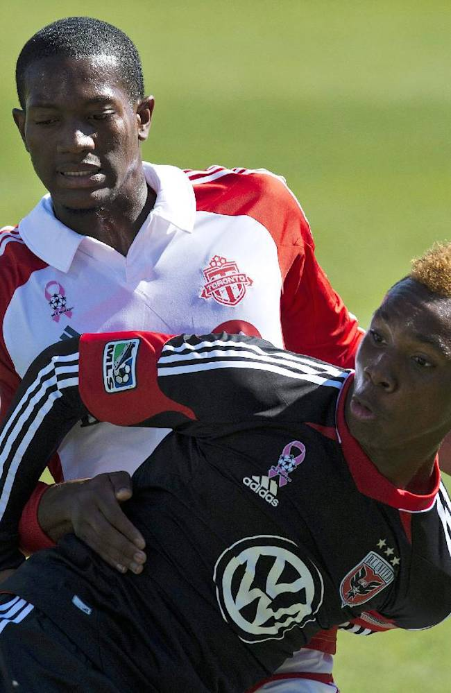 CORRECTS MONTH - Toronto FC defender Donel Henry, rear, and D.C. United forward Michael Seaton battle for a ball during the first half of an MLS soccer game against Toronto FC in Toronto on Saturday, Sept. 28, 2013