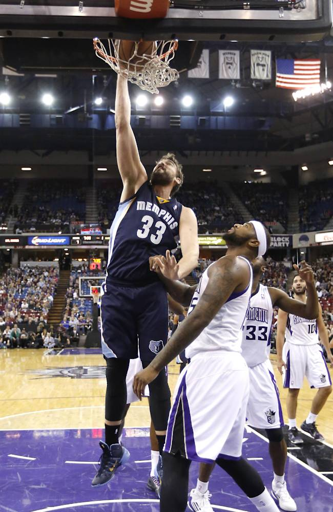 Memphis Grizzlies center Marc Gasol, left, of Spain, stuffs over Sacramento Kings center DeMarcus Cousins during the first quarter of an NBA basketball game in Sacramento, Calif., Sunday, Nov. 17, 2013