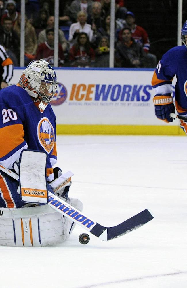 New York Islanders goalie Evgeni Nabokov, of Kazakhstan, makes a save against the Montreal Canadiens as center Frans Nielsen (51) of Denmark looks on in the first period of an NHL hockey game at Nassau Coliseum in Uniondale, N.Y., Saturday, Dec. 14, 2013