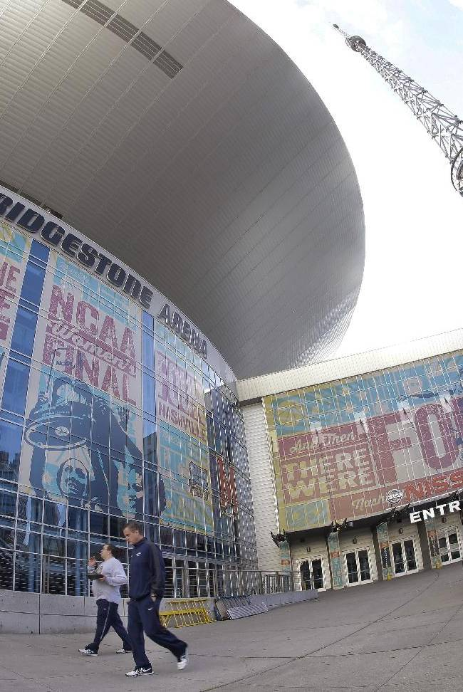 In this photo made with a fisheye lens, people walk past Bridgestone Arena on Friday, April 4, 2014, in Nashville, Tenn., where the Final Four of the NCAA women's college basketball tournament will be played. The semifinals are scheduled for Sunday