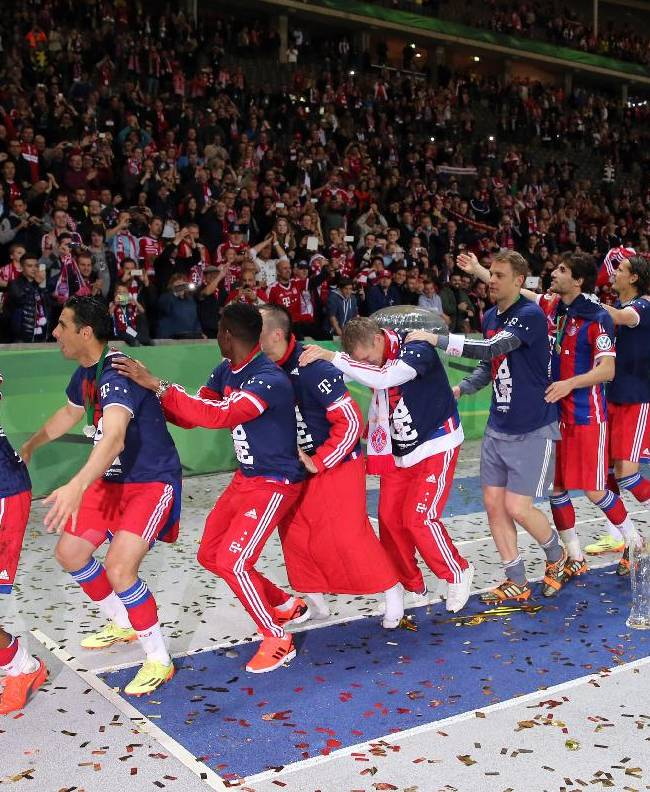 In this picture taken Saturday May 17, 2014, Bayern Munich's soccer player Dante, left, holds  the German soccer cup, as other teammates dance in joy , after winning the German soccer cup final against Borussia Dortmund in Berlin
