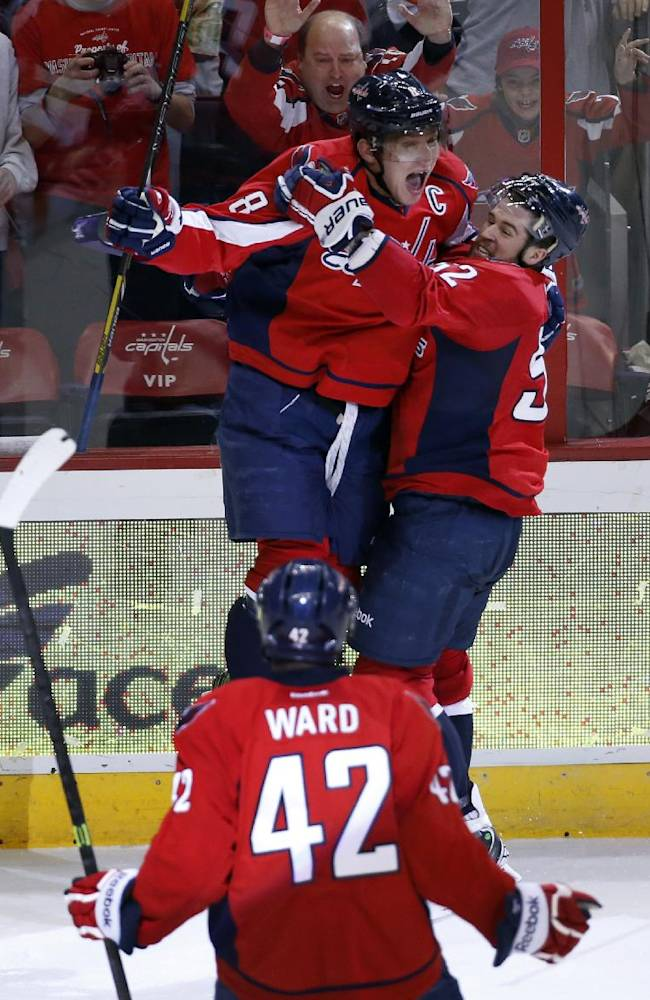 Washington Capitals right wing Alex Ovechkin (8), from Russia, celebrates his goal with defenseman Mike Green (52) as right wing Joel Ward (42) comes comes join them, in the third period of an NHL hockey game, Sunday, Dec. 15, 2013, in Washington. Ovechkin's goal sent the game into overtime and the Capitals won 5-4 in a shootout