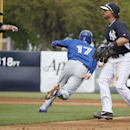 Second base umpire Clint Fagan, left, calls Toronto Blue Jays' Ryan Goins (17) out as New York Yankees second baseman Brian Roberts, right, watches in the fifth inning of a spring exhibition baseball game in Tampa, Fla., Sunday, March 23, 2014 The Associa