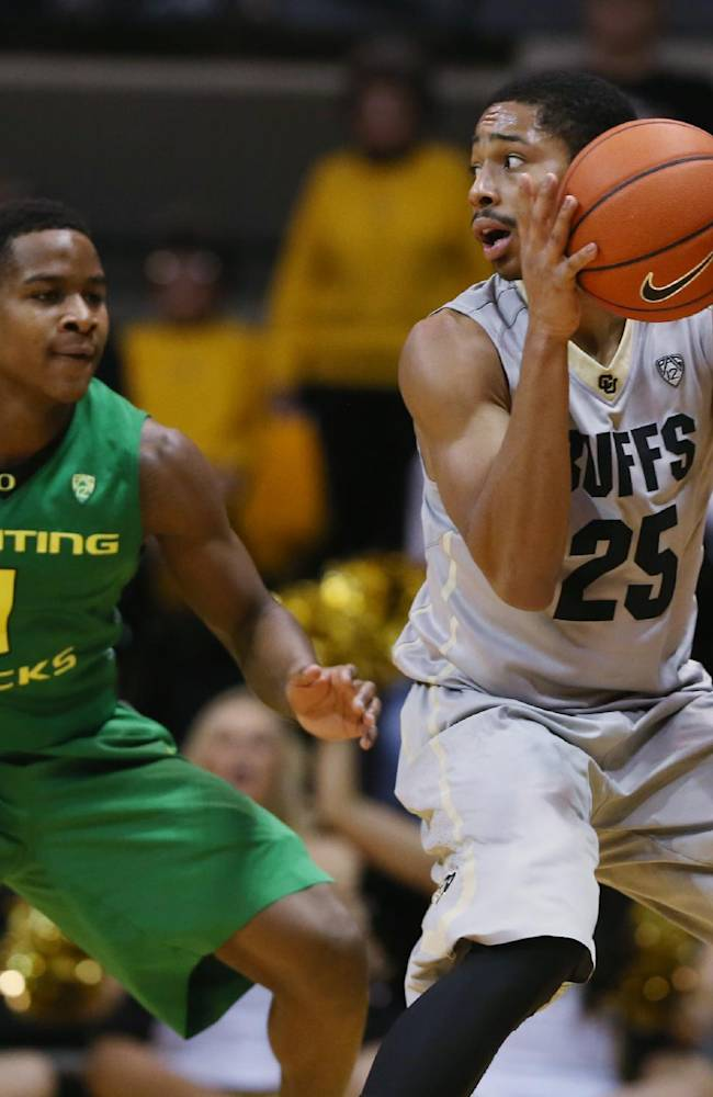 Colorado guard Spencer Dinwiddie, right, pulls in the loose ball as Oregon guard Dominic Artis defends in the second half of Colorado's 100-91 victory of an NCAA college basketball game, Sunday, Jan. 5, 2014, in Boulder, Colo