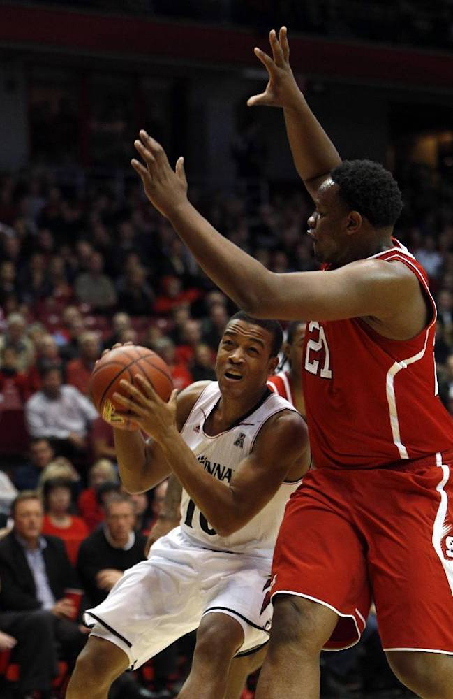 Cincinnati guard Troy Caupain, left, is pressured by North Carolina State forward Beejay Anya during the first half of an NCAA college basketball game Tuesday, Nov. 12, 2013, in Cincinnati