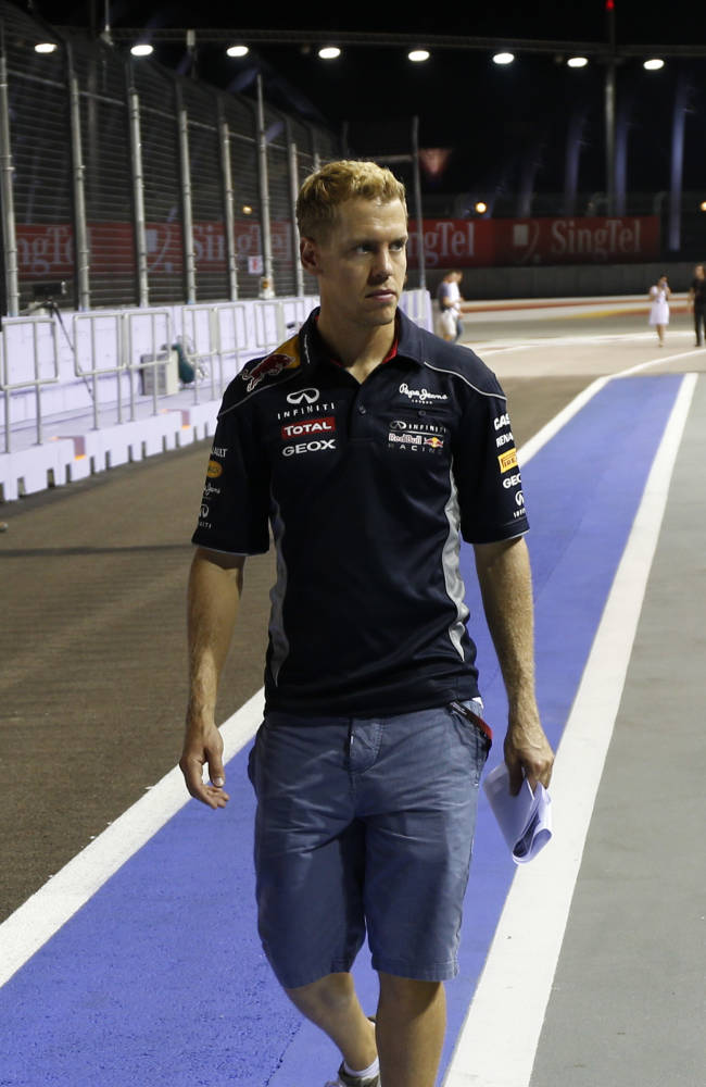 Red Bull driver Sebastian Vettel of Germany walks on the Marina Bay Circuit on Thursday, Sept. 19, 2013, in Singapore, ahead of the Formula One Singapore Grand Prix to be held Sunday Sept. 22, in the city-state